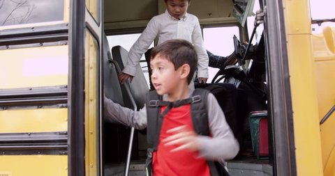 Young elementary school kids getting off a school bus
