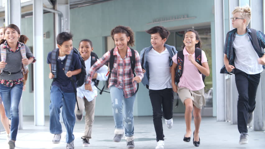 Group of 5th grade school kids running in a school corridor