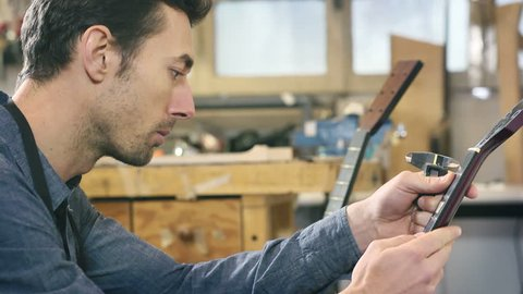 Young man at work as craftsman in italian workshop with guitars and musical instruments. Rack focus