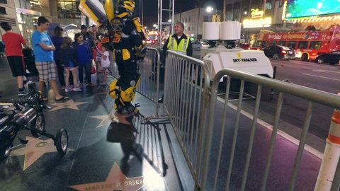 HOLLYWOOD, CA - December 9, 2015: Bumblebee transformer robot impersonator in costume talking to cop on Hollywood Boulevard at night. 4K UHD.