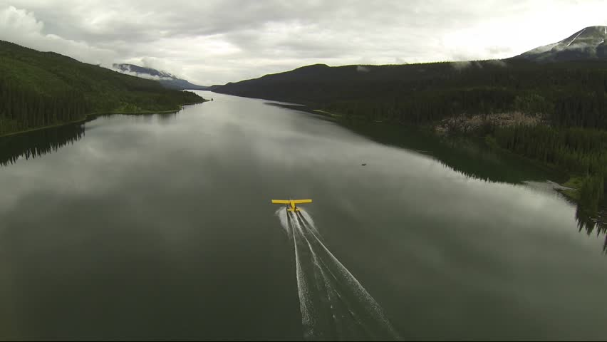 AERIAL CHASE SHOT OF FLOAT PLANE TAKE OFF IN LAKE BC CANADA