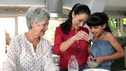 Little girls, grandma and his mom preparing a cake in the kitchen