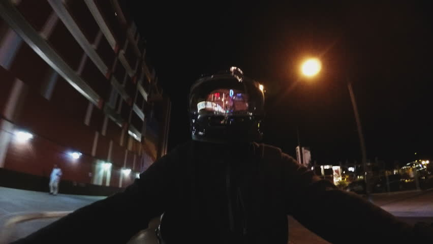 """LAS VEGAS, NEVADA/USA: May 3, 2015-A 'selfie"""" shot of a night motorcycle rider cruising under the bright lights of East Fremont Street."""