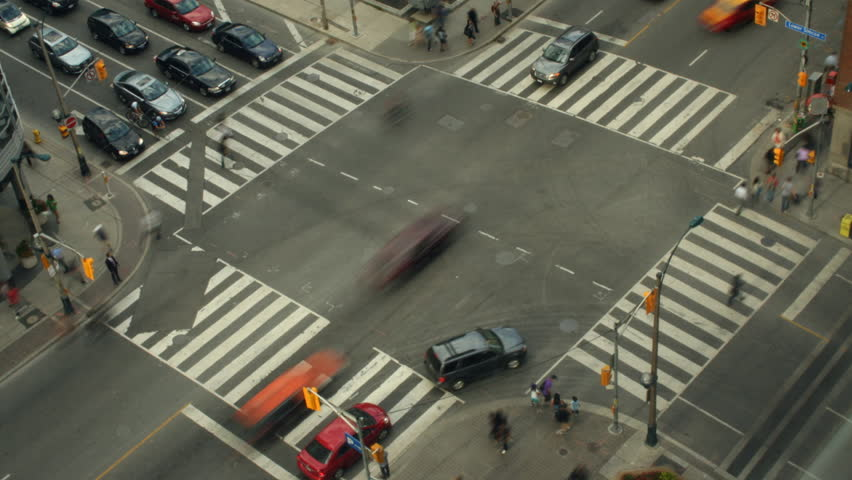 Intersection of Front and Simcoe in downtown Toronto with vehicles and pedestrians crossing on an overcast day. Shot in time-lapse. All recognizable logos have been blurred for your convenience. | Shutterstock HD Video #1639657