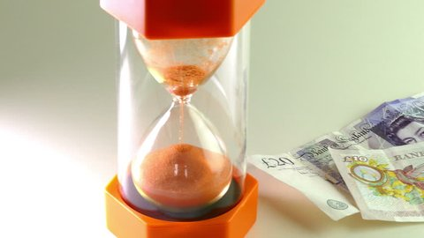 'Time is money' or 'Time running out' concept. Slider shot across sterling and a bright orange sand timer.