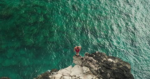 Aerial view cliff jumping into ocean, summer lifestyle fun