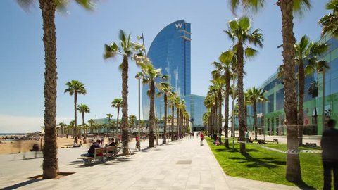 Barcelona, Spain - May 1, 2016: 4K Hyperlase (timelapse) approaching the facade of the W Barcelona (Hotel Vela) through palm trees, located in the Barceloneta district, next to the beach.