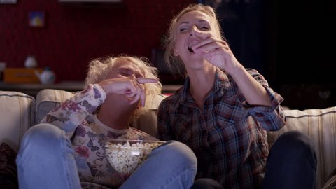 Two girls friends watching a movie on TV, eating popcorn and laugh