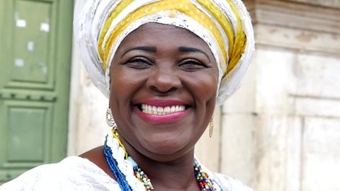Brazilian woman of African descent wearing traditional clothes from the state of Bahia in the old colonial district of Salvador (Pelourinho), Brazil