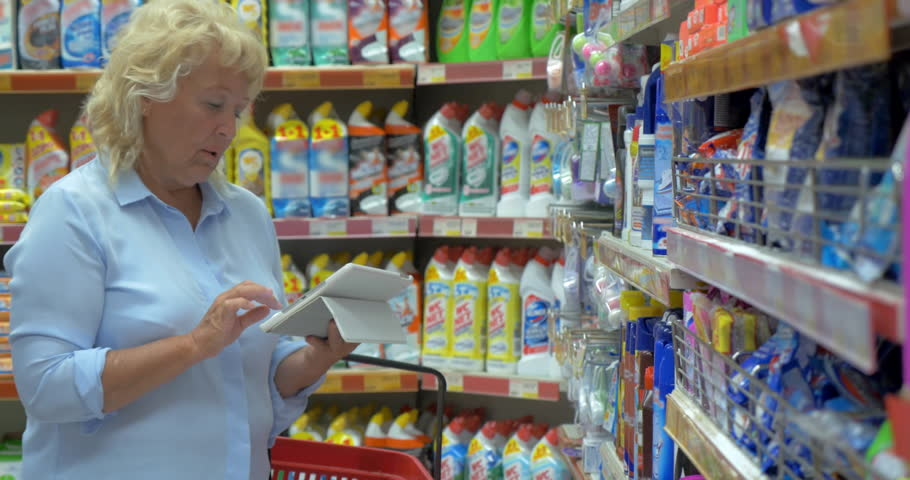Happy senior woman using tablet computer while choosing household cleaning products in the supermarket | Shutterstock HD Video #16482727
