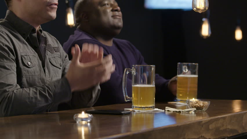 Two guys cheering for their team at a bar | Shutterstock HD Video #16527787