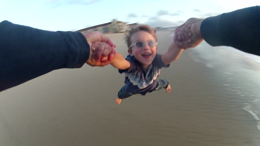 POV of a father holding his son's hands and spinning him around on the beach at sunset. - Model Released - 1920x1080 - Full HD