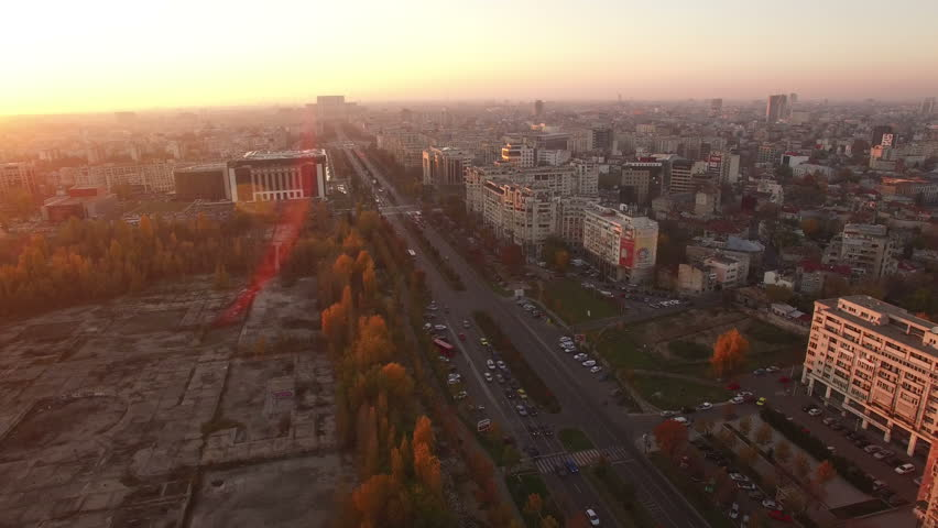 Aerial view over Bucharest City center skyline with Unirii Boulevard, National Library, Dambovita River and House of Parliament or House of People on the background at dusk.