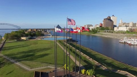 MEMPHIS, TENNESSEE - APRIL 11, 2016: Flying over the waving flags in Memphis. Mississippi river and cityscape in background