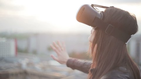 woman uses a virtual reality glasses on the roof