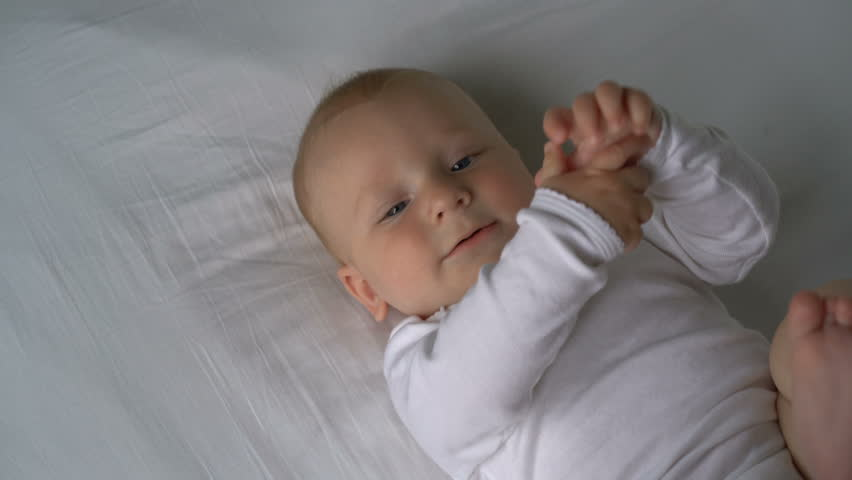 Mother tickles the baby and he laughs lying on the bed | Shutterstock HD Video #16624066