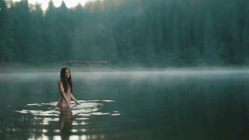 Beautiful naked fairy or mermaid with long dark hair touches the surface of mystical foggy mountain lake and combing her long hair. Fantasy magic world in mountains
