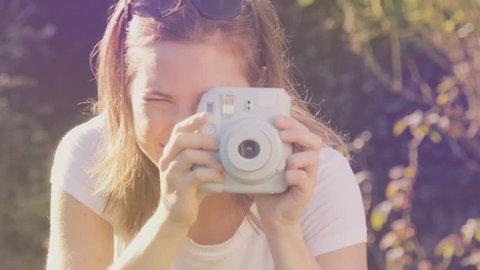 Portrait of hipster girl holding retor insta polaroid camera taking photo