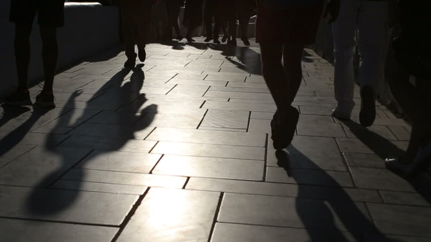 Shadows of people walking in city. Street procession.