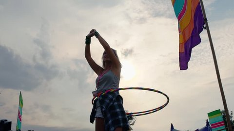 Girl hula-hooping at a music festival, slow motion