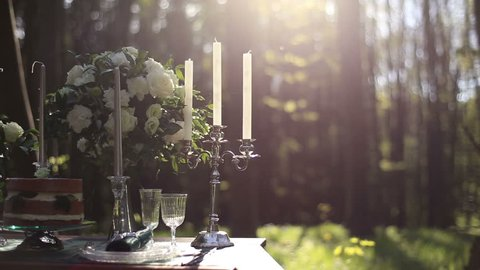 Close up of white vintage candelabrum on the wedding decorated table in the forest. Bouquet of white roses on background. Romantic dinner in the forest