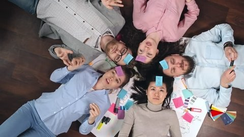 Directly above view of young team with sticky notes on their foreheads lying on floor in circle and playing Who am I game, shot on Sony NEX 700 + Odyssey 7Q