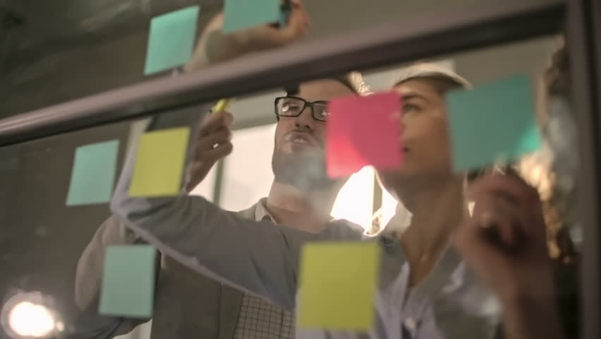 Young business team brainstorming and writing down ideas on sticky notes attached to glass wall, shot on Sony NEX 700 | Shutterstock HD Video #16739896