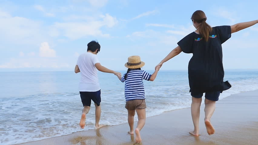 Slow motion of Happy Asian family running on the sand beach together, Phuket Thailand