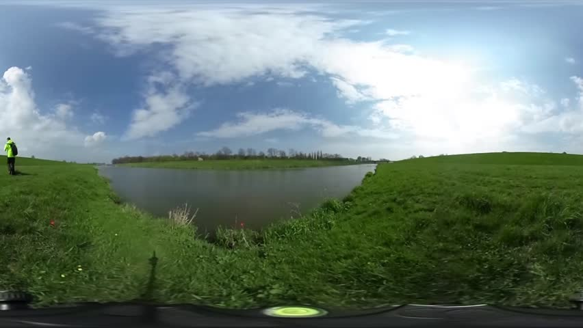 Man is Walking by a Green Lawn, Hills Around a Water, Spherical Panorama Video, vr Video 360, Little Planet Video, Video For Virtual Reality, Landscape, Man in Lemon Yellow Sporty Jacket, Lake or