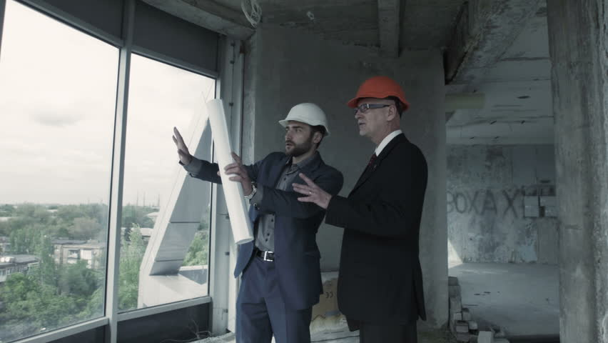 Young manager of the construction company goes through the two men in suit and helmet discuss blueprint calculate and communicate with colleague american malvernweather Images