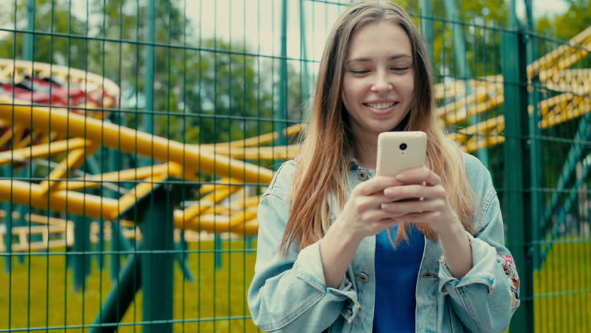 Girl with the phone against the backdrop of a theme park | Shutterstock HD Video #16783753