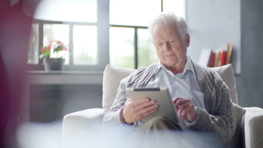 old man is using tablet computer at home