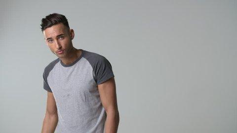 Young man in t-shirt runs hand through hair, turns, waist up