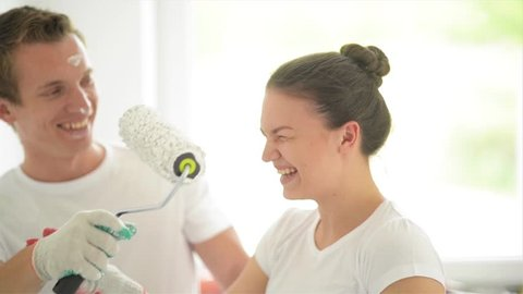 Beautiful couple paint the walls in a new apartment, laughing and having fun. Young family makes repairs in their new flat