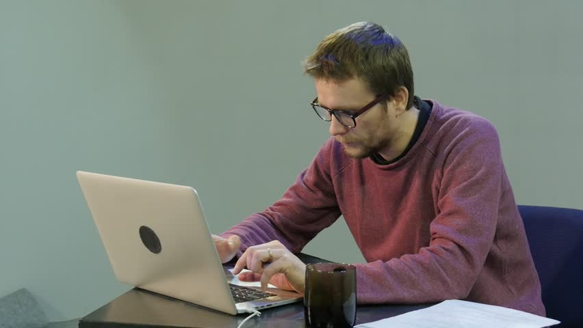 Man Working With Laptop Touches His Chin and Thinking, Male Freelancer, Programmer, Copywriter, Designer, Accountant is Working Hard With His Face Concentrated, Cup of Tea is on a Table, Young Man is | Shutterstock HD Video #16820557