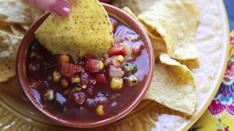 Dipping tortilla chip into fresh salsa with corn and black beans.