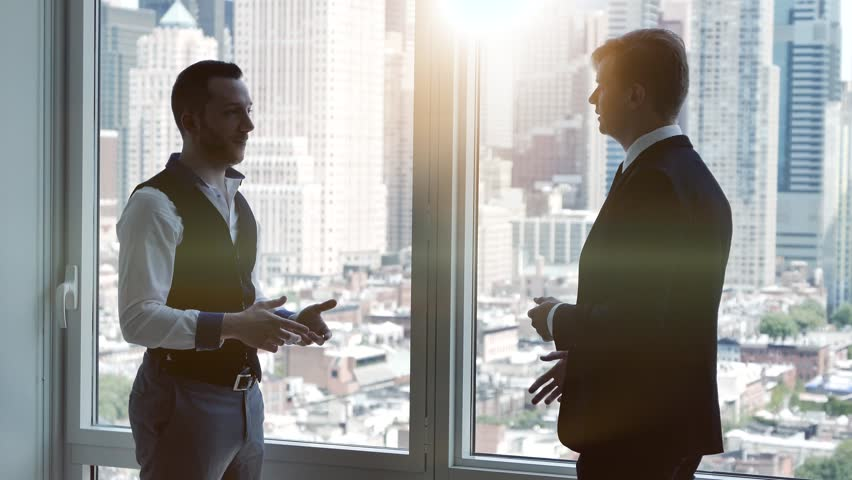 Two young businessman having a meeting in modern city office standing on window front. business people talking about financial profits growth concept    Shutterstock HD Video #16832137