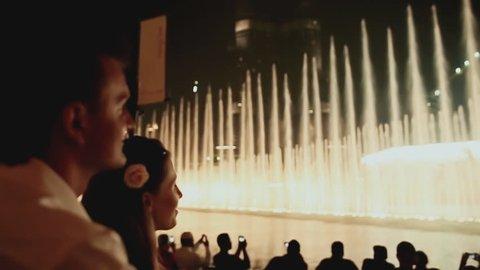 DUBAI, UAE - NOVEMBER 13: The girl and the guy look at fountains in Dubai at night on November 13, 2015 in Dubai, UAE