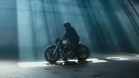 Young Caucasian male biker in leather jacket driving his custom cafe racer motorcycle in large warehouse garage. 60 FPS slow motion Blackmagic URSA Mini RAW graded footage
