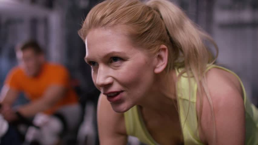 4K Close up of woman working out on exercise bike at the gym. Shot on RED Epic. UK - April, 2016