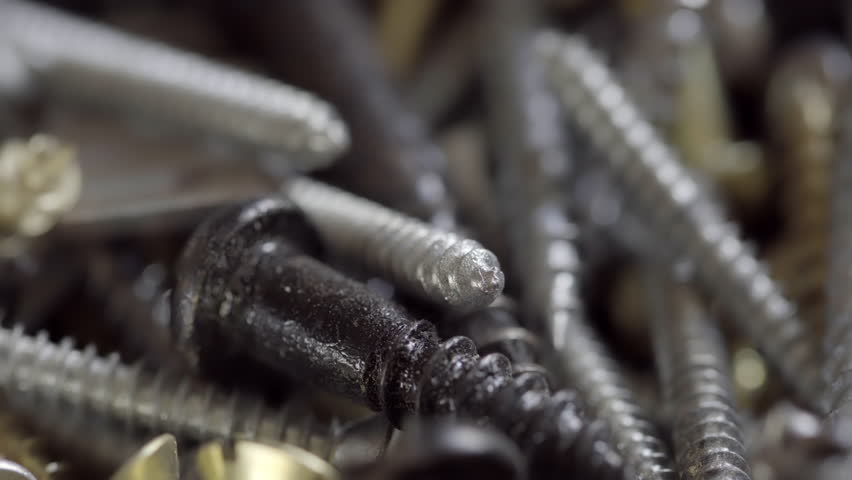 Collection of screws background UHD stock footage. Assortment of various screws in true macro close up with a rotating camera move. | Shutterstock HD Video #16915159