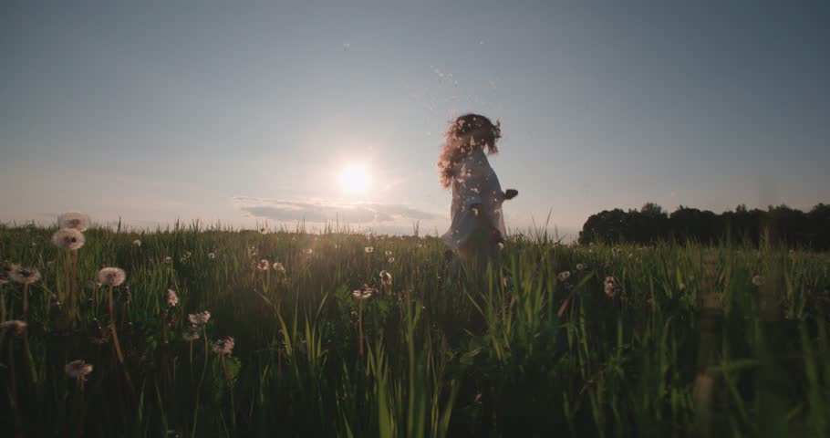 Beautiful young woman ran in the Dandelion field at sunset, slow motion