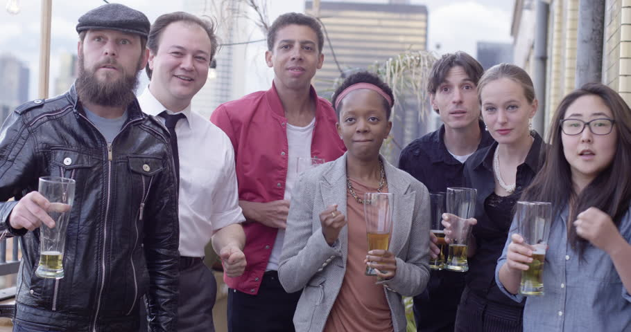 Group of mixed race and gender friends celebrate a victory as an event unfolds off-screen in front of the Downtown Los Angeles skyline at sunset.  Medium shot, recorded in slow motion at 60fps.