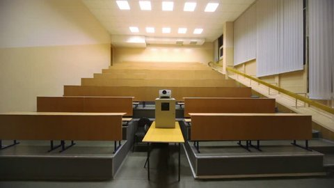 Light turned off, and then switched on, in empty lecture auditorium, white projector and wooden furniture on several levels