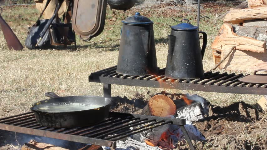 Civil War era cooking setup with kettles and skillet on racks with campfire
