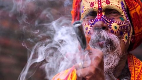 Portrait of sadhu smoking marijuana out of his pipe, Pashupatinath temple complex in Kathmandu, Nepal. This temple is the oldest Hindu temple in Kathmandu, and it sits on the bank of the Bagmati River