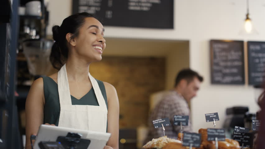 4K Cheerful worker serving a customer who uses smartphone to pay in coffee shop. UK - April, 2016 | Shutterstock HD Video #16996087