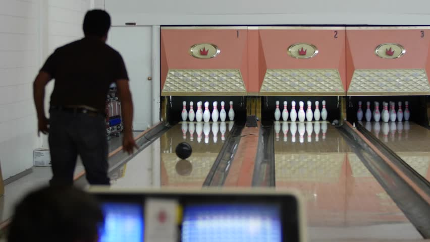 People playing a game of bowling at the small town bowling alley