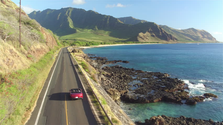 AERIAL: Red convertible car driving along the coastal road above dramatic rocky shore towards volcanic mountains. Happy young couple on summer vacation traveling at the seaside in Oahu island, Hawaii | Shutterstock HD Video #17029471