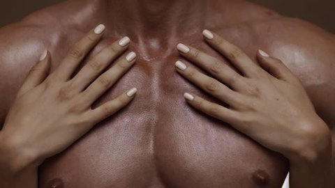 Hands of young woman touching athletic torso with abs of man. Graded